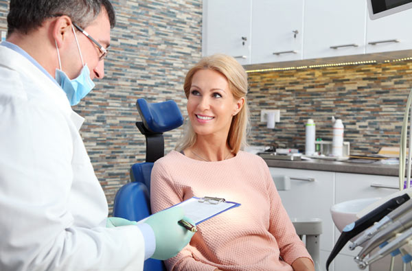 Woman talking to dentist during dental exam at D.A. Dental in Auburn, MA.